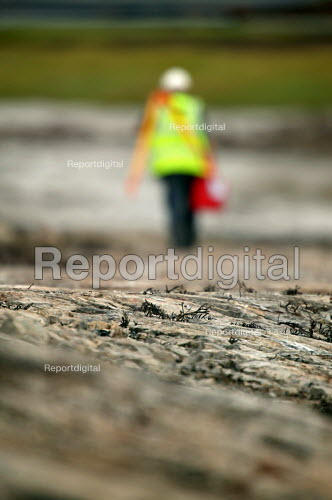 Surveyor at work. A sewage outlet pipe is cut ithrough rock on the severn estuary near the severn bridge crossing. - Paul Box - 2004-08-02