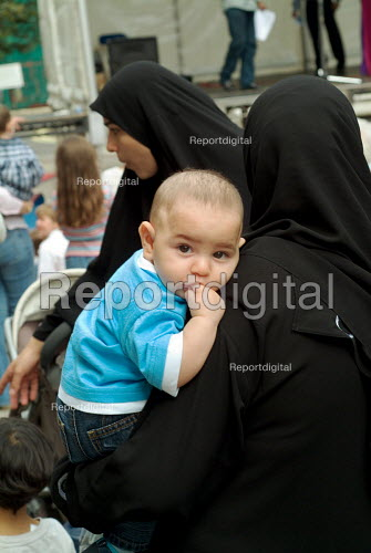 A Muslim woman in a hijab carries a small child at a community festival Paddington, London. - Philip Wolmuth - 2004-08-22