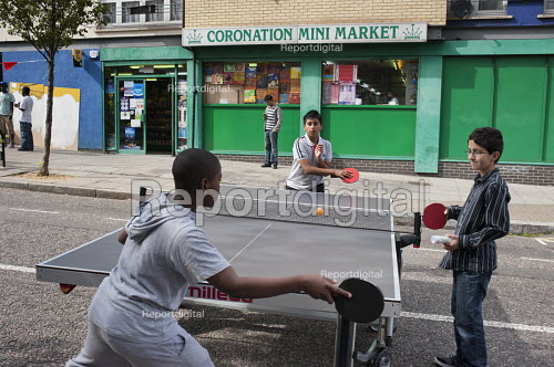 Children play table-tennis at a Tell It Parents Action Group street event to launch a drop-in advice service on the Mozart Estate, North Westminster, which has experienced problems with postcode gang violence. - Philip Wolmuth - 2011-08-22