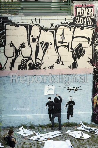 A street artist (name unknown) wearing a hoodie uses stencils to create a mural of children attacked by a drone in the style of Banksy on a wall bordering a well-used footpath along the Danube Canal, Vienna. - Philip Wolmuth - 2014-07-03
