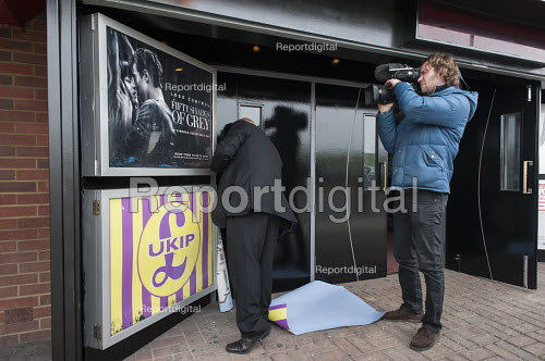 A member of staff removes UKIP posters outside the Movie Starr cinema, Canvey Island, South Essex, following the launch of the party's General Election campaign a the seafront venue. - Philip Wolmuth - 2015-02-12