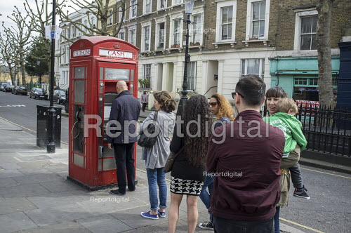 Queue for an ATM cash machine in a telephone box, a combined public payphone and cash machine. London. - Philip Wolmuth - 2015-04-10