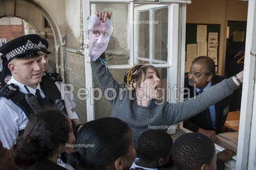 Police officers watch as Blue 9 private security guards prevent protesters from entering Hendon Town Hall through a window. Tenants, evicted tenants and housing campaigners in Barnet, north London, protest over the sale of West Hendon estate and the demolition of Sweets Way estate. - Philip Wolmuth - 2015-05-13