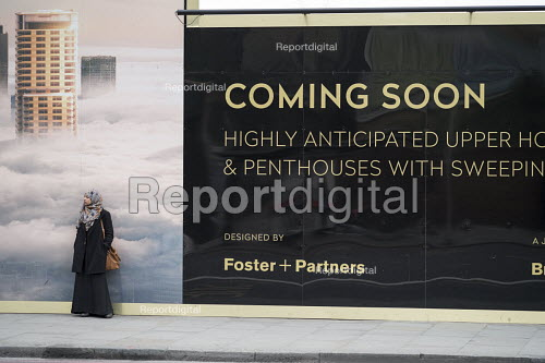 Woman waiting for a bus by a hoarding advertising new luxury housing by Foster and Partners, Shoreditch, London. - Philip Wolmuth - 2015-05-07