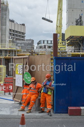 Construction workers taking a break Rathbone Square office retail and residential redevelopment by Great Portland Estates behind Oxford Street London. - Philip Wolmuth - 2015-08-19