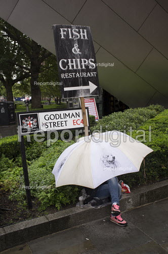 Tourist with an umbrella in heavy rain, fish and chips sign City Of London - Philip Wolmuth - 2015-08-25