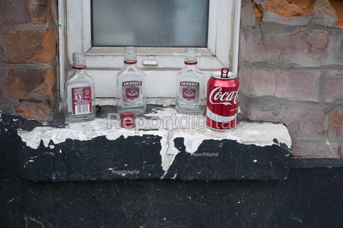 Empty Smirnoff vodka bottles left by street drinkers on a window ledge north London - Philip Wolmuth - 2015-08-27
