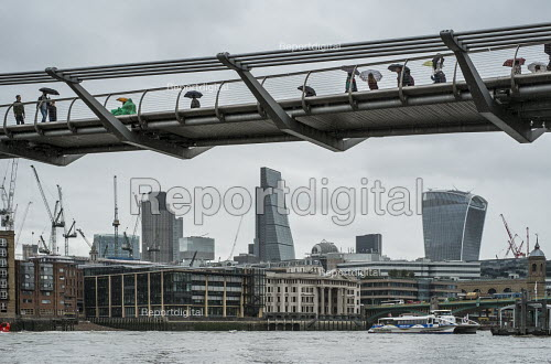 Tourists with umbrellas on the Thames Millennium Bridge London in heavy rain - Philip Wolmuth - 2015-08-25