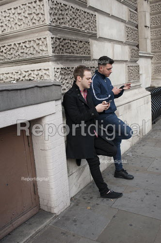 Two young men leaning on a wall check mobile phones in a London street - Philip Wolmuth - 2015-09-29
