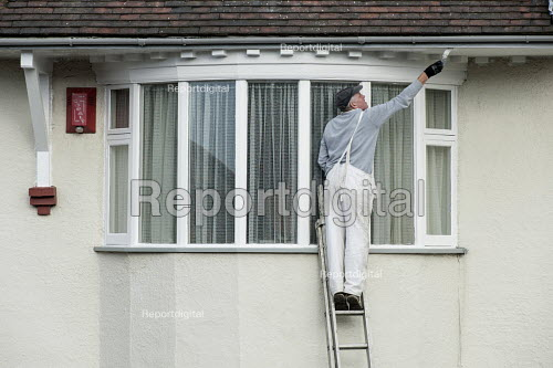 Painter up a ladder painting a house, Camden, London - Philip Wolmuth - 2015-10-13