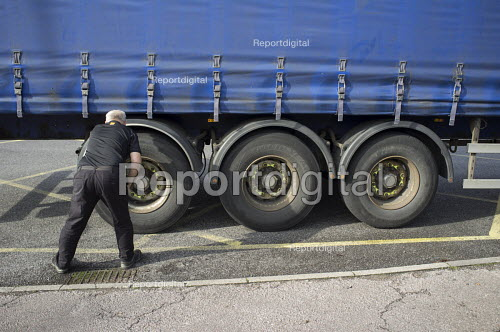 Lorry driver checking his tyres on a London street - Philip Wolmuth - 2015-10-28