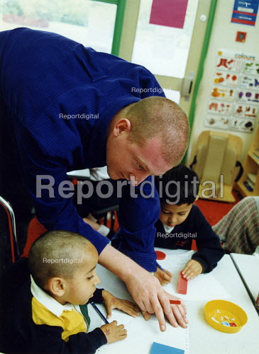 Teacher helping a pupil, at integrated primary school, East London - Joanne O'Brien - 20021024