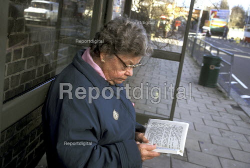 Elderly woman reading a book at bus stop - Joanne O'Brien - 20021024