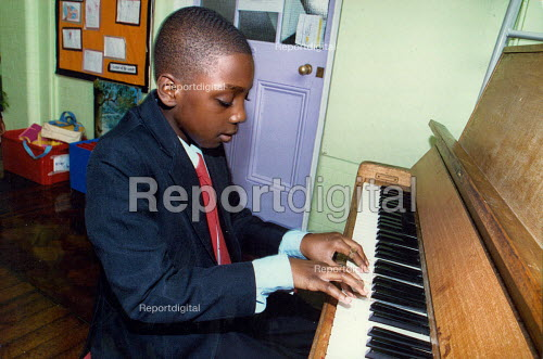 Primary school pupil learning to play the piano. - Joanne O'Brien - 20021024