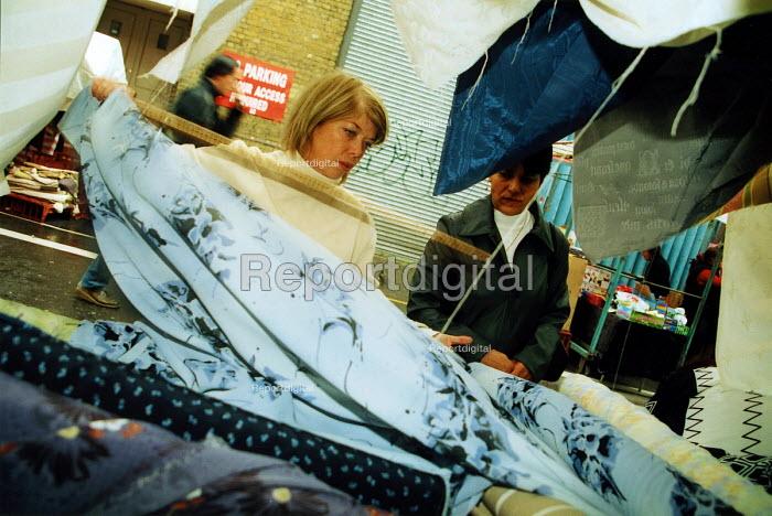 Market trader measuring fabric Leather lane London - Joanne O'Brien - 20021210