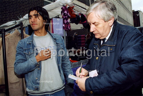 Market inspector issuing daily permit to stall holder Leather Lane London - Joanne O'Brien - 20021210