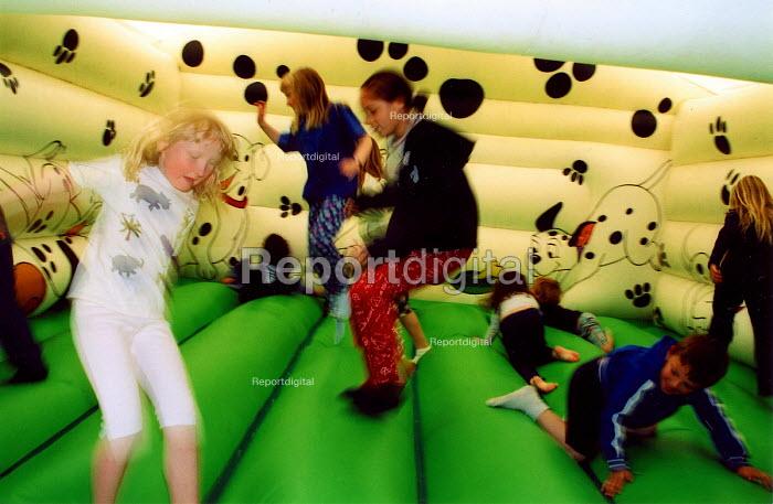 Children playing in bouncy castle. School Open day, London - Joanne O'Brien - 2002-06-02