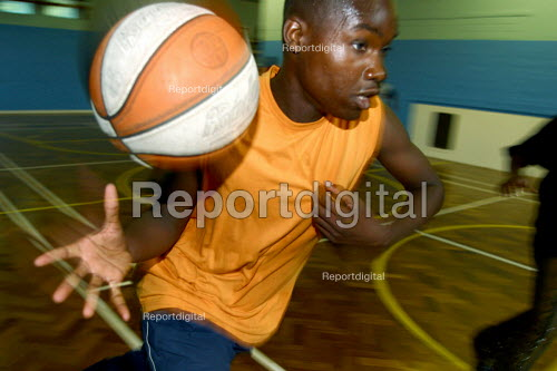 Boys play basketball at sports summer scheme for youth in Haringay, London - Joanne O'Brien - 20021024