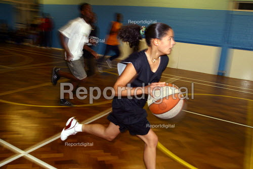 Girl playing basketball at sports summer scheme for youth in Haringay, London - Joanne O'Brien - 20021024