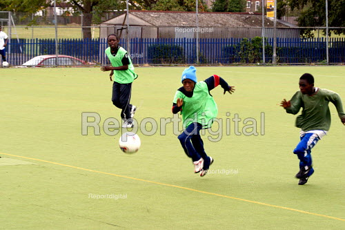 Boys playing football at sports summer scheme for youth in Haringay, London - Joanne O'Brien - 20021024
