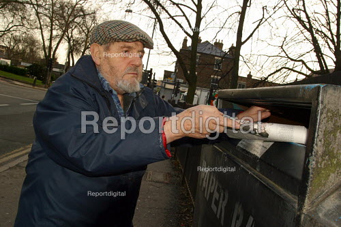 Elderly man recycling papers into street bin. London - Joanne O'Brien - 2004-03-24