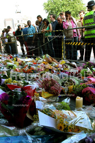 Kings Cross Station, central London. Flowers for those who died in the bombings. A member of the public look on - Joanne O'Brien - 2005-07-09