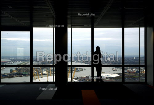 Man on telephone in empty floor of tower block, at Canary Wharf with a view of the City of London - Joanne O'Brien - 2007-11-28