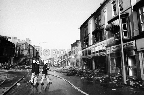 Firefighters hosing down buildings set on fire the night before, Handsworth riots 1985, burnt out buildings and cars litter the area, with debris scattered across the streets - John Harris - 1985-09-10