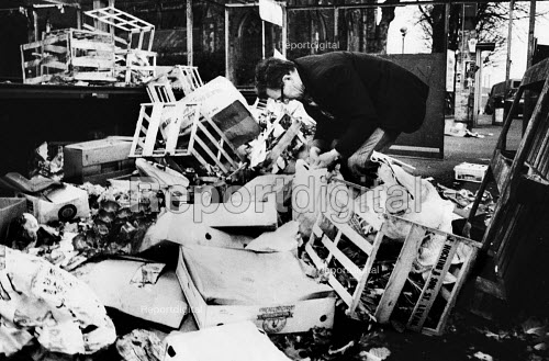 A man mooching - looking for food amongst the market traders' discarded rubbish at the end of the day in the Bull Ring shopping area of Birmingham, 1987. - John Harris - 1987-03-12