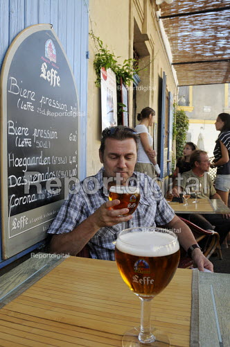 Customer drinking a glass of Leffe Beer at a table at a cafe in Arles in southern France. - Stefano Cagnoni - 2011-08-06