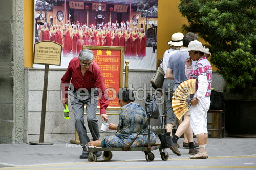 A severely disabled man begging outside the Jade Buddha Temple, Shanghai - Timm Sonnenschein - 2010-08-12