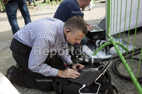Press photographer Joel Goodman editing and sending photographs from his laptop. TUC march against austerity cuts and unfair Trade Union Bill, Conservative Party Conference, Manchester. - Timm Sonnenschein - 2015-10-04