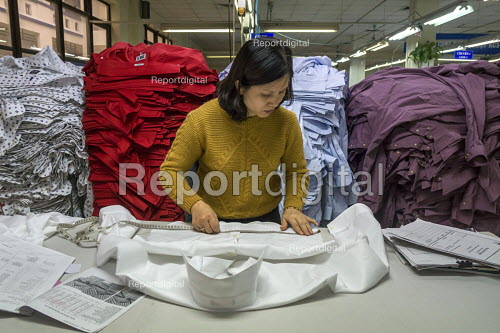Hanoi Vietnam worker checks the quality of sewing in garments, May 10 Garment Factory. The factory was state owned when it began 29 years ago and is now half-owned by private capital. It makes garments for LExpress, FOB and other mostly American companies. About 2500 workers work in the Hanoi factory. - David Bacon - 2015-12-15