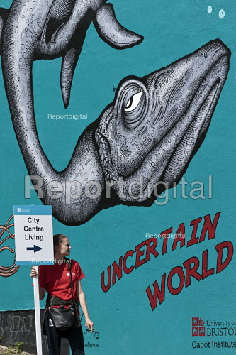 Student with an open day sign, City Centre Living, University of Bristol. Cabot Institute mural Uncertain World by Alex Lucas on climate change and global warming leading to a rise in sea levels - John Harris - 2016-06-17