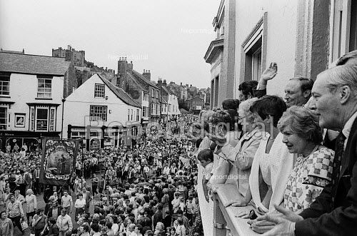 "Durham Miners Gala, 1983. Miners and their families march on the 100th Anniversary of the Durham Miners Gala or ""Big Meeting"". Labour Party leaders, including Tony Benn & Neil Kinnock, wave to the procession from the balcony of The County Hotel - Stefano Cagnoni - 1983-07-16"