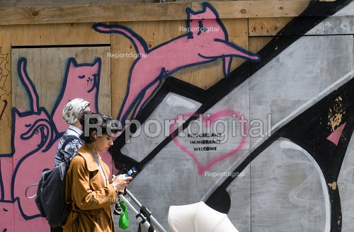 Pink Cats alongside graffiti proclaiming Refugees and Immigrants Welcome, Stamford Hill, London. Post-Brexit message in London on a hoarding welcoming refugees and immmgrants into the UK. - Stefano Cagnoni - 2016-07-05