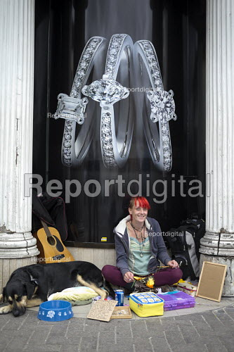 Homeless woman selling dreamcatchers below an advertisement for diamond rings in a closed shop doorway, Stratford-upon-Avon - John Harris - 2016-09-09