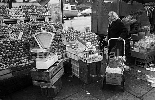 Pensioner looking at prices on a street market fruit and veg stall ,Tower Hamlets, one of the poorest boroughs in the UK, London 1976 - Angela Phillips - 1976-02-12
