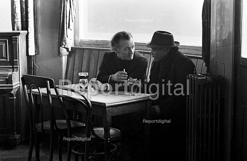 Two men drinking and talking in a run down pub at lunchtime, Tower Hamlets, one of the poorest boroughs in the UK, 1976 - Angela Phillips - 1976-02-12