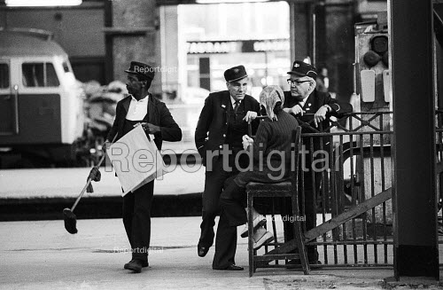 British Rail porters enjoying a quiet moment to talk, Kings Cross Station, London 1977 - Derek Speirs - 1977-04-12