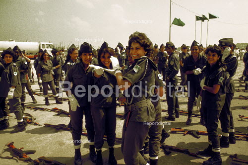 Demonstration in support of Muammar Gaddafi, Tripoli 1984 on the 15th Anniversary of the coup that put him in control of Libya, later renaming it the Socialist Peoples Libyan Arab Jamahiriya. Female soldiers from the Special Womens Milita enjoing a lighter moment during the demonstration. - Stefano Cagnoni - 1984-09-01