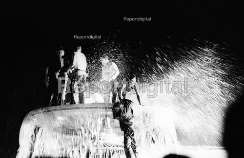 Labour Party victory in 1966 General Election. Crowds jumping into the fountains celebrating Labour General Election win in Trafalgar Square broadcast live on BBC TV on screen in the Square - Patrick Eagar - 1966-03-31