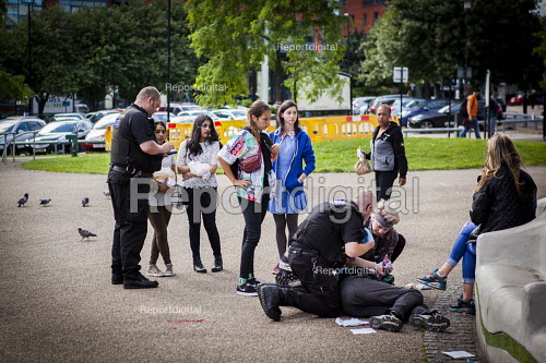 Man who has been assulted as he sat on a bench in theCity Centre being helped by tPolice officers. Sheffield centre, South Yorkshire - Connor Matheson - 2016-07-13
