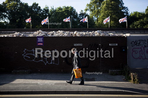 A man walking to work by rubble and the union jacks. Sheffield city center, South Yorkshire - Connor Matheson - 2016-08-16