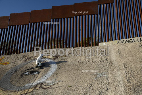 Nogales, Sonora Mexico, graffiti artists paints a mural below the U.S.-Mexico border fence. - Jim West - 2016-10-08