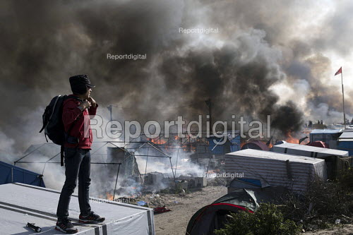 Young refugee watches fires rage during the eviction of the Jungle camp, Calais, France. - Jess Hurd - 2016-10-26