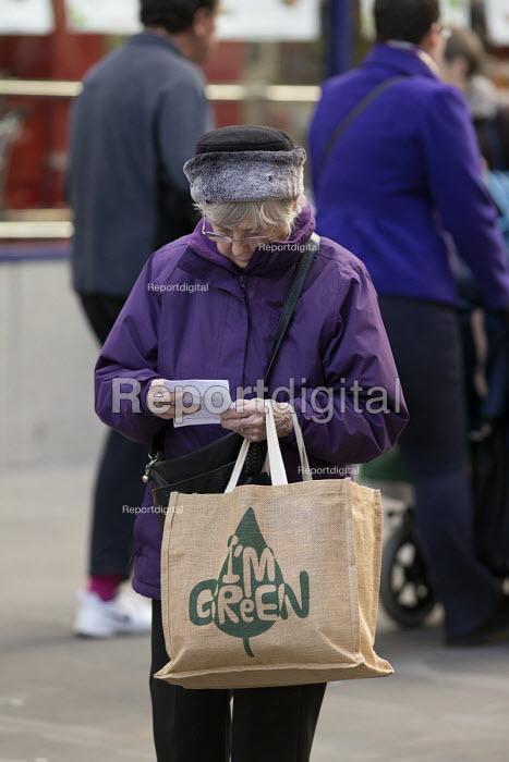 Elderly woman with Green hessian shopping bag and list, Swindon Shopping precinct, Wiltshire - John Harris - 2016-12-16