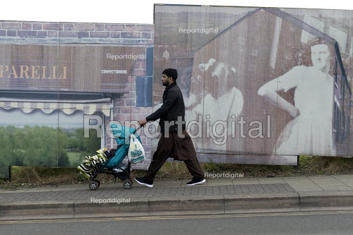 Man with pushchair walking past picture boards in front of house demolition, Hanley, Stoke on Trent, Staffordshire - John Harris - 2017-02-17