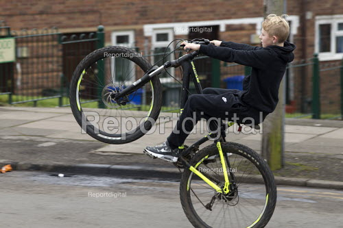 Boy pulling wheelies on his bicycle, Bentilee, Stoke on Trent, Staffordshire - John Harris - 2017-02-18