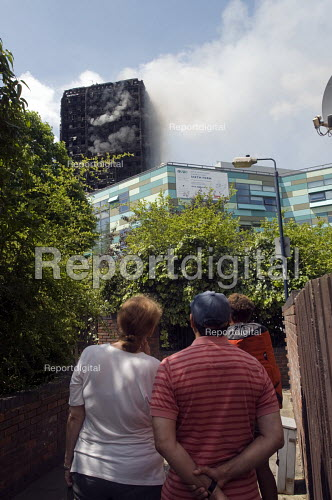 Grenfell Tower Fire. Local residents watch on as smoke still smoulders a full 12 hours after the raging inferno that engulfed the West London tower block resulting in the loss of many lives - Stefano Cagnoni - 2017-06-14